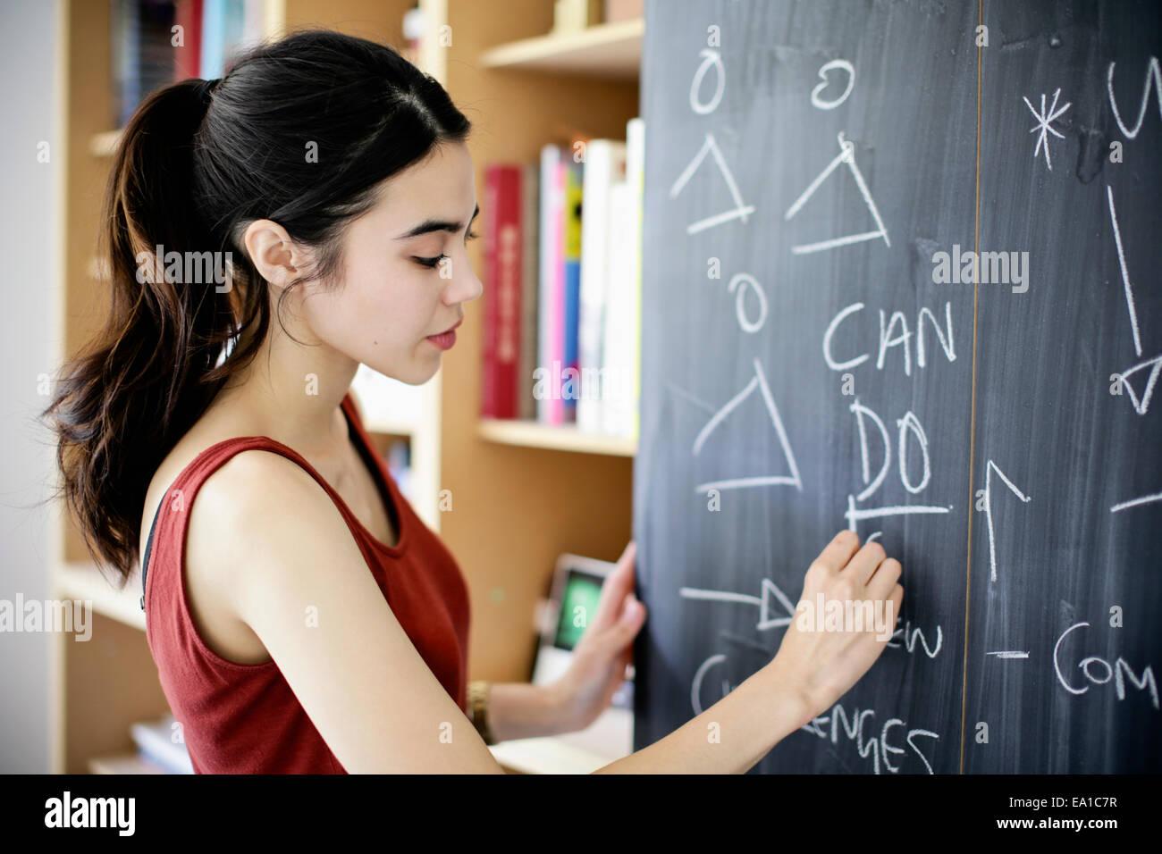 Frau an Tafel schreiben Stockbild