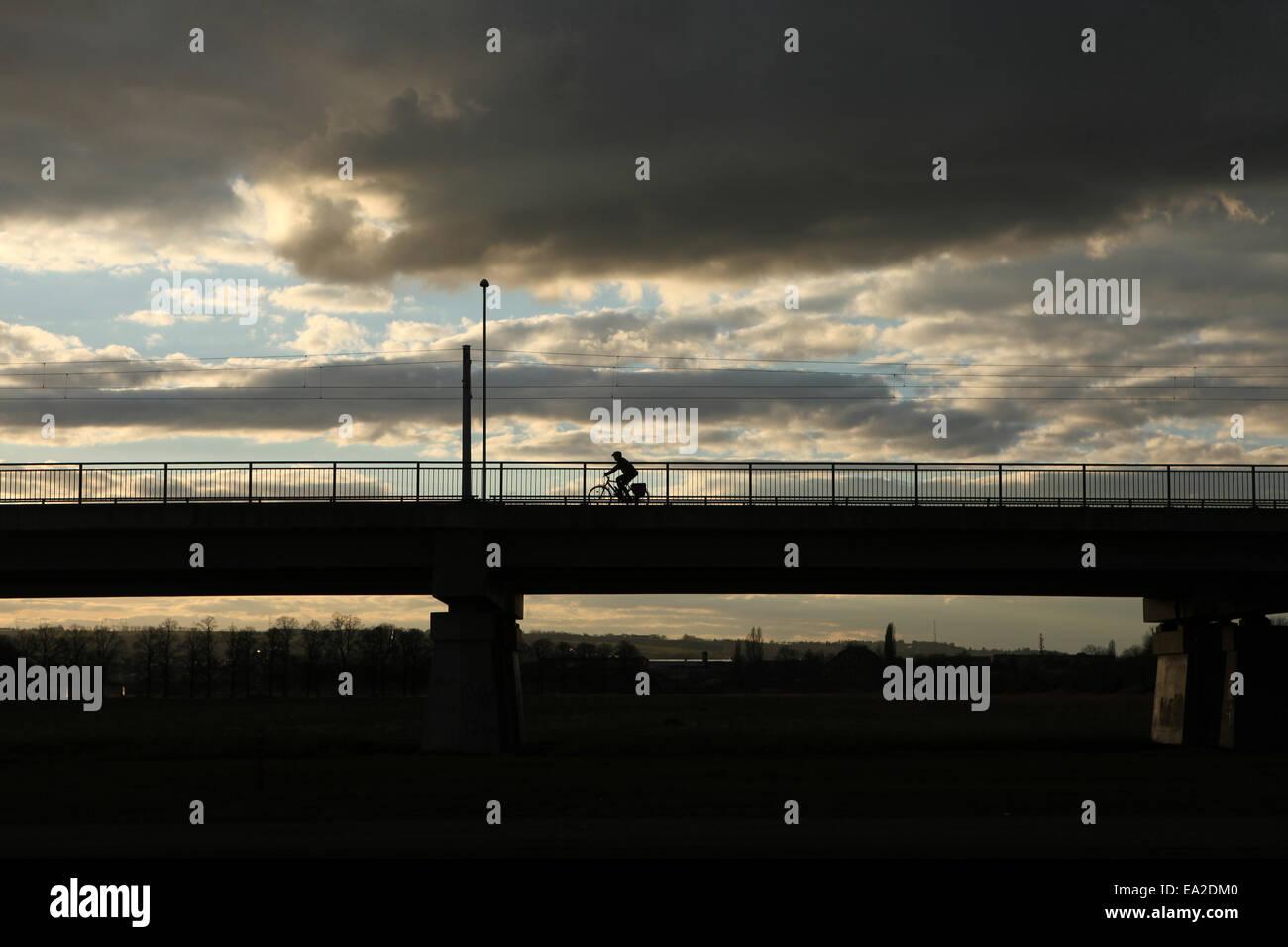 Biker geht auf der Brücke über die Elbe bei Sonnenuntergang in Dresden, Sachsen, Deutschland. Stockbild