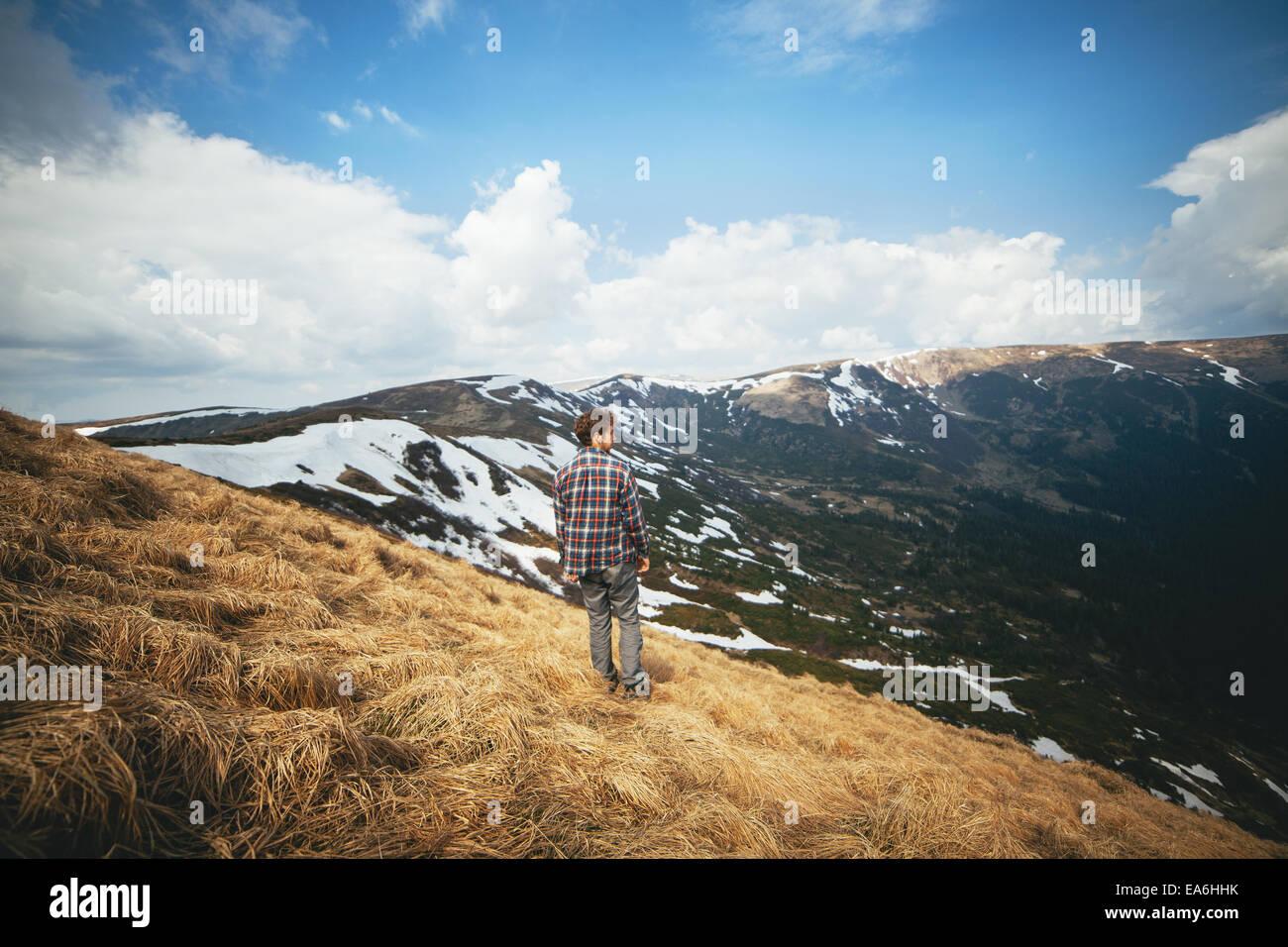 Junger Mann im Feld stehen und betrachten Stockbild