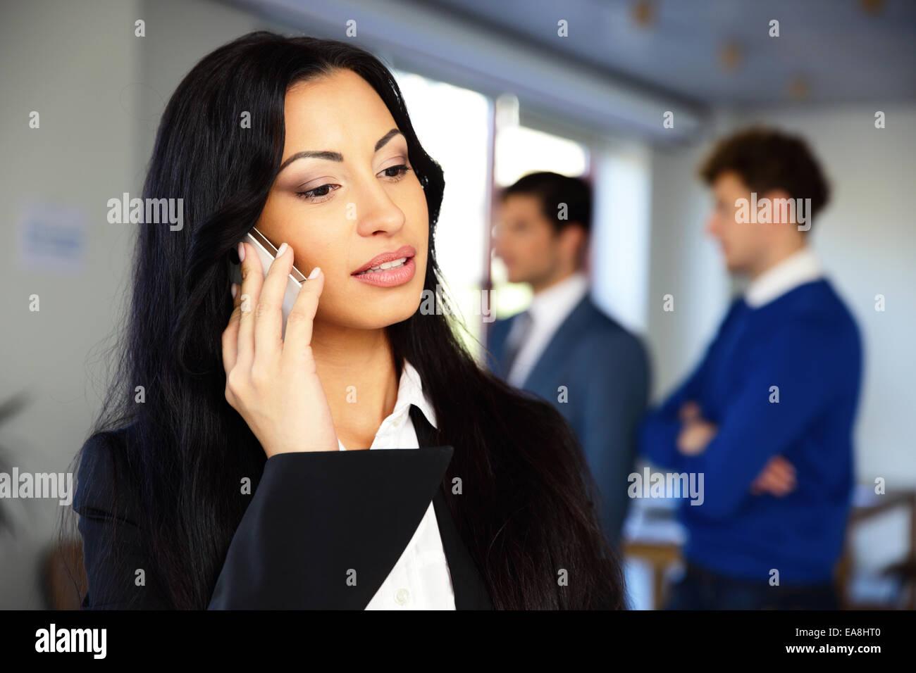 Ernsthafte Geschäftsfrau mit Kolleginnen und Kollegen im Hintergrund am Telefon sprechen Stockbild