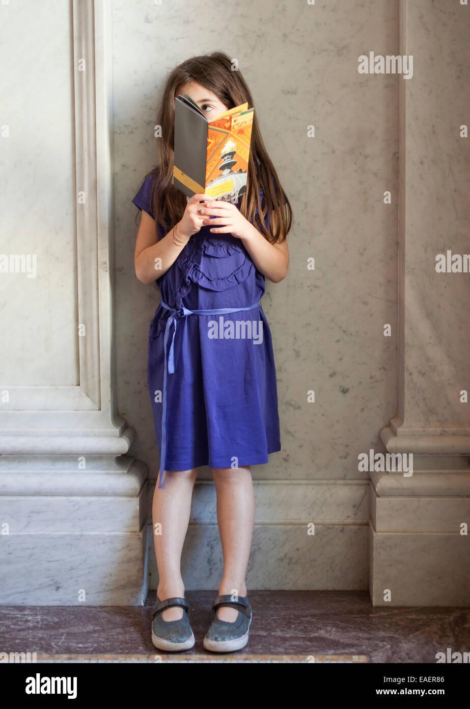 junge Mädchen stehen in Marmor-Lobby eine Broschüre lesen und schaut sich um Stockbild