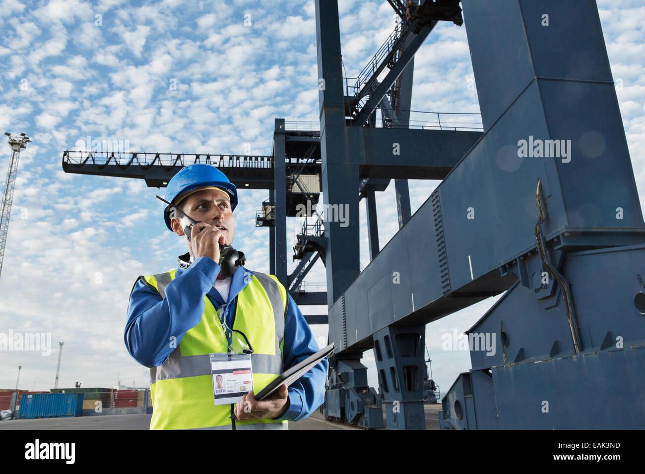 Arbeiter mit Walkie-talkie unter Ladung Kran Stockbild
