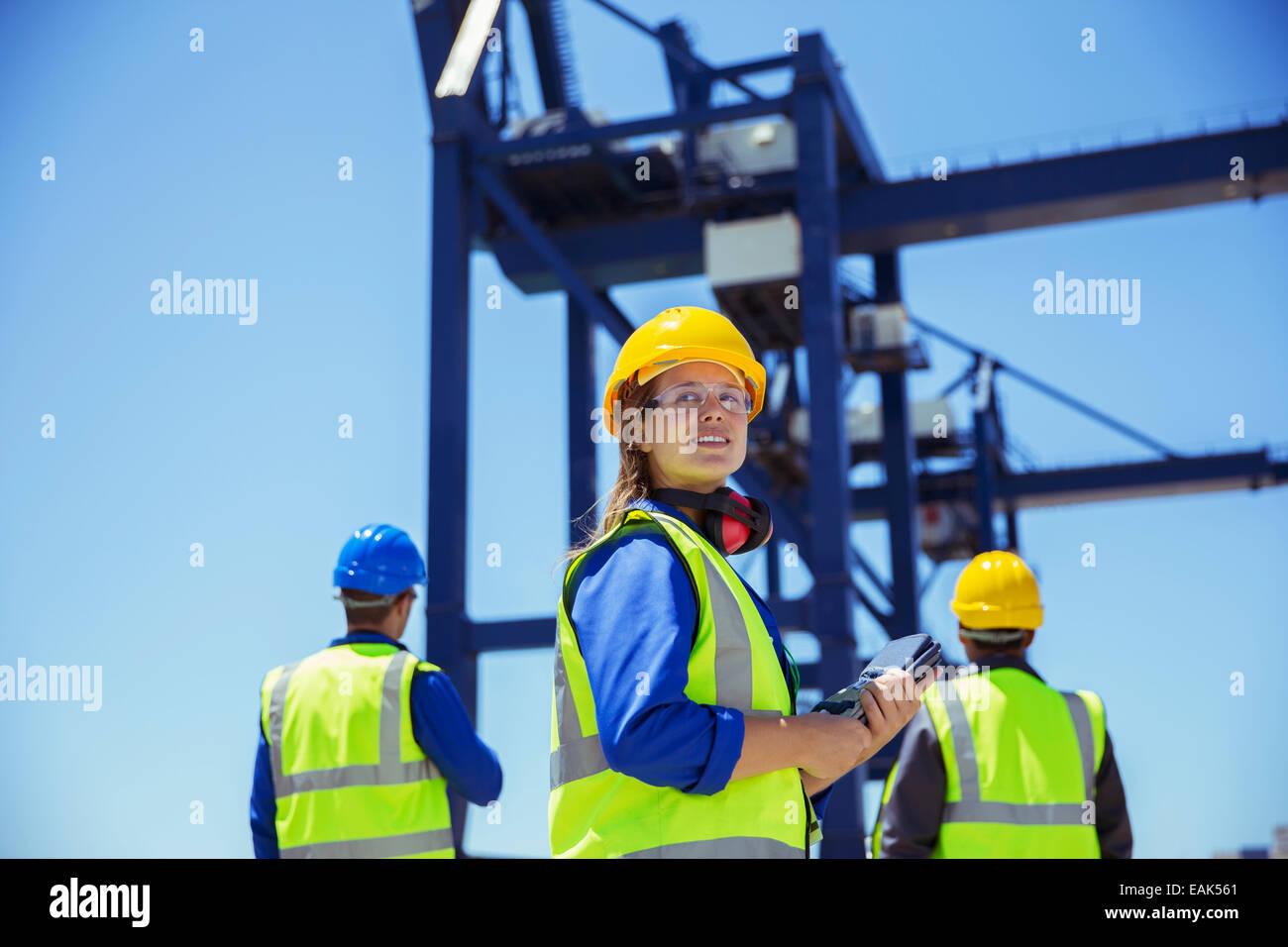 Niedrigen Winkel Ansicht der Arbeitnehmer unter Ladung Kran steht Stockbild