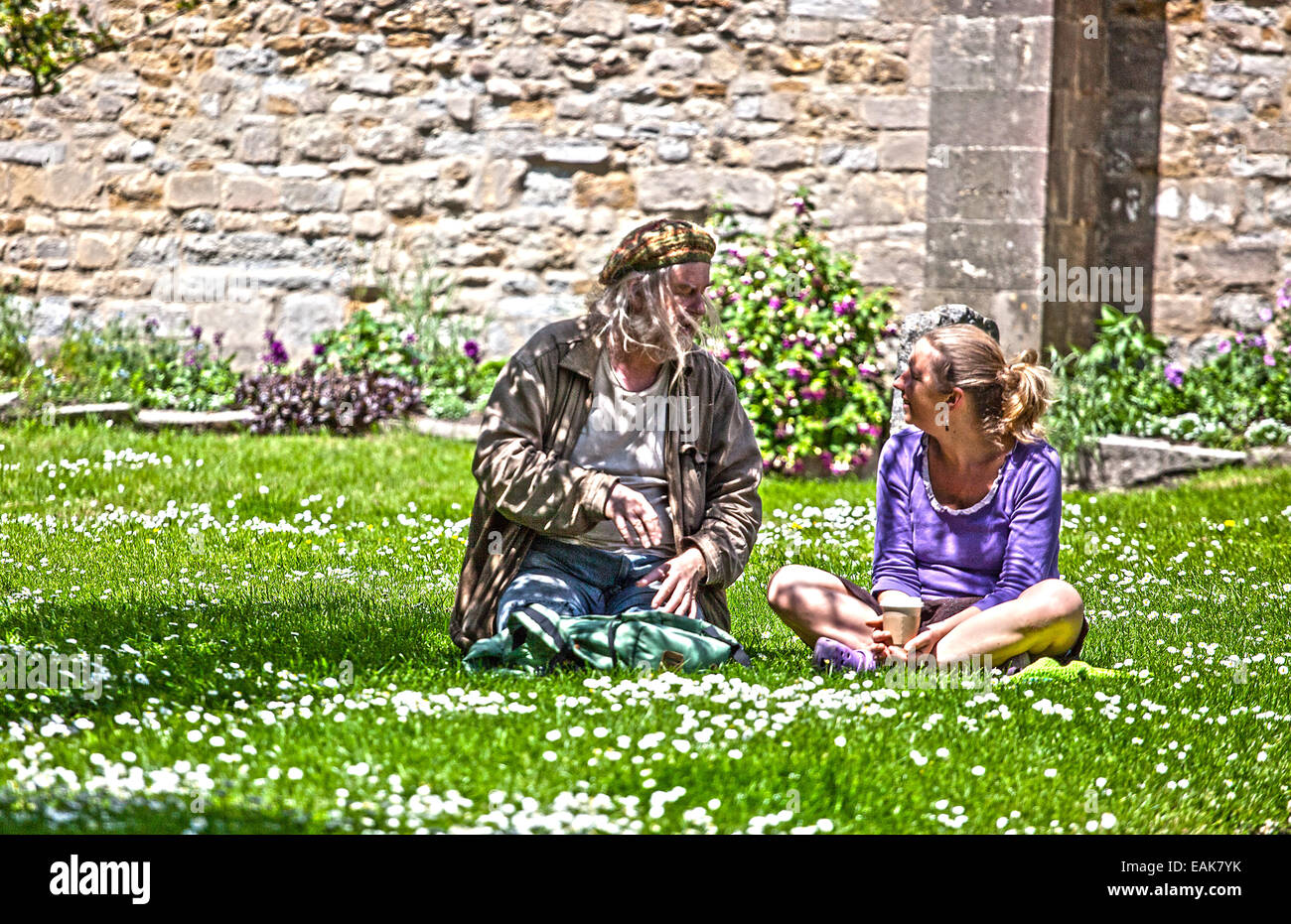 2 Menschen PPE, ein Weibchen, 1 Männchen sitzen in einem Feld und reden im Vereinigten Königreich im Sommer. Stockbild