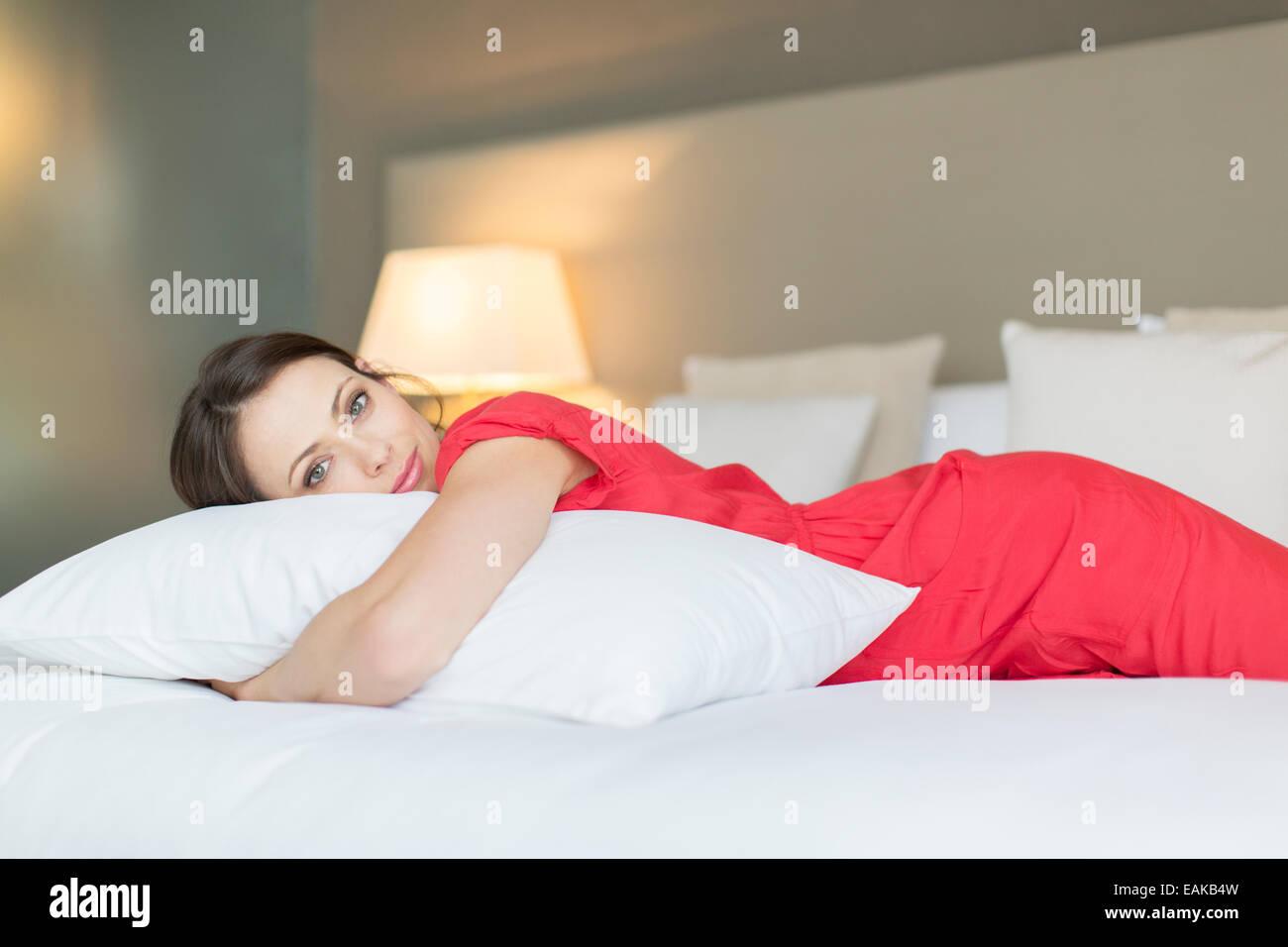 Portrait der schönen Frau roten Kleid auf Bett liegend und Kissen umarmt Stockbild