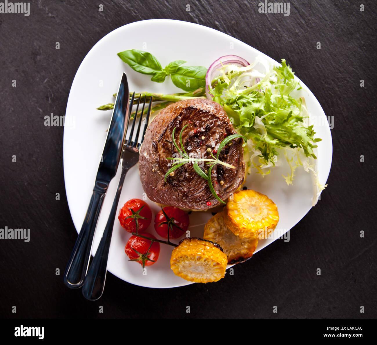 Stück rotes Fleisch Steak mit Gemüse, Kräutern und Gewürzen, serviert auf schwarzem Steinoberfläche. Stockbild