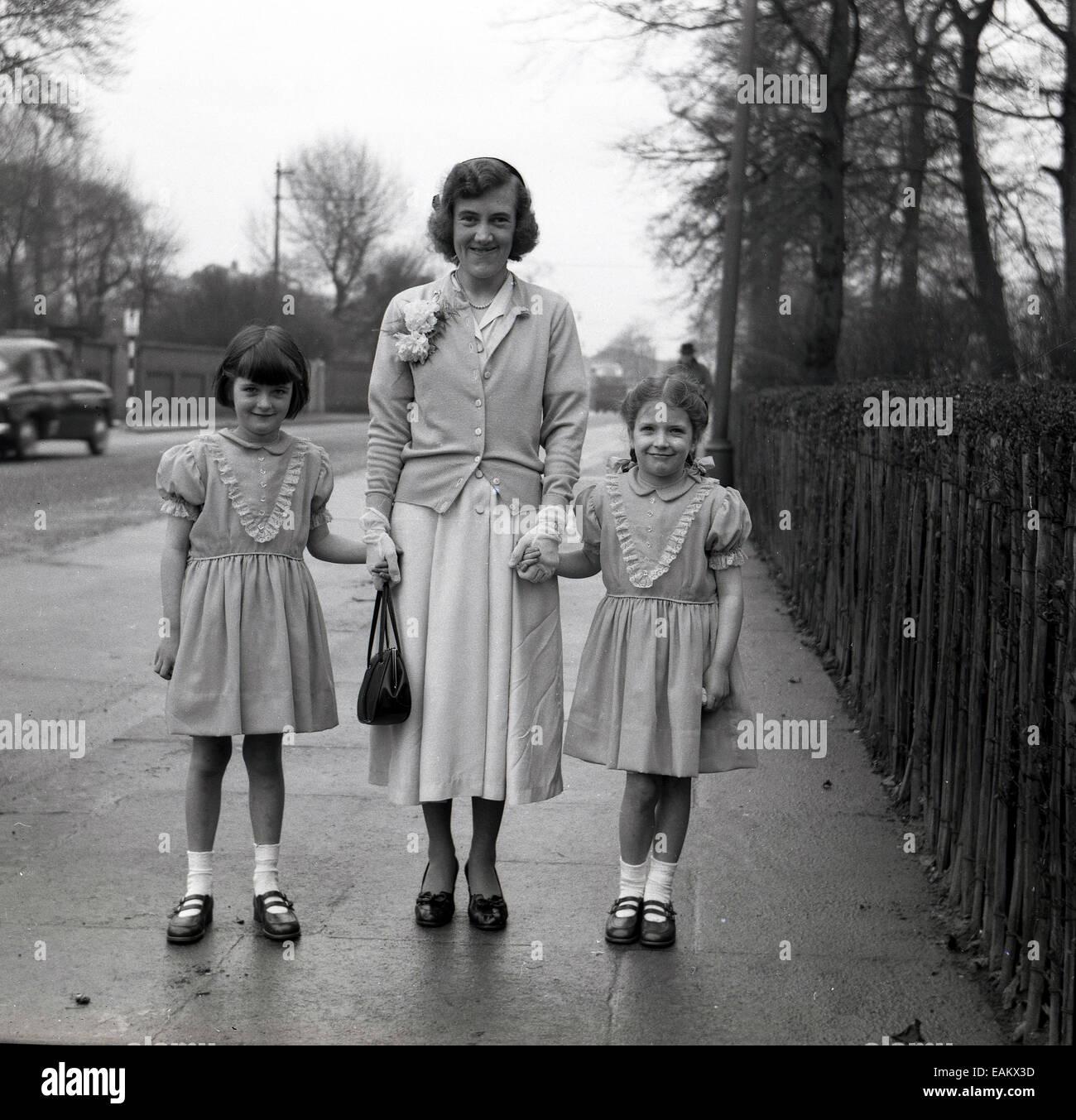 1950er Jahre historische Bild einer Mutter stehend auf einem Bürgersteig mit ihren zwei kleinen Kindern, kleine Stockbild