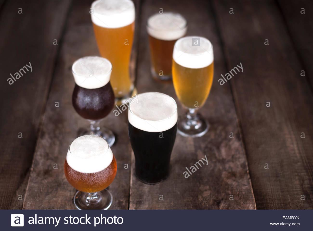 Auswahl an Bieren in einer Vielzahl von Glaswaren auf rustikale Oberfläche des Holzes. Stockbild