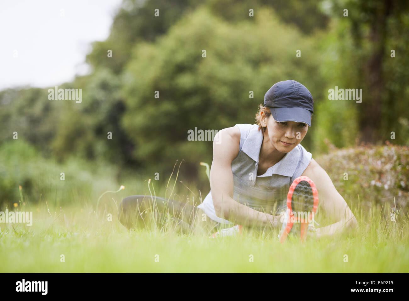Eine Frau, die Vorbereitung für Bewegung in der Natur, dehnen. Stockbild