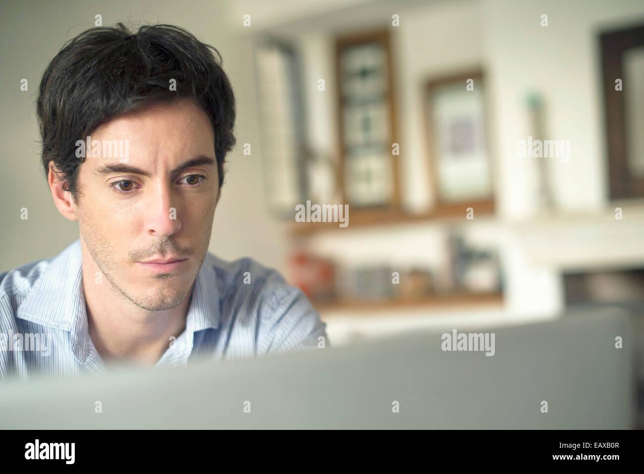 Mann starrte auf Laptop-computer Stockbild