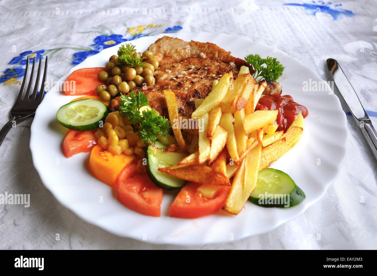 Ungesunde Mahlzeit von Hähnchen mit Pommes Stockbild