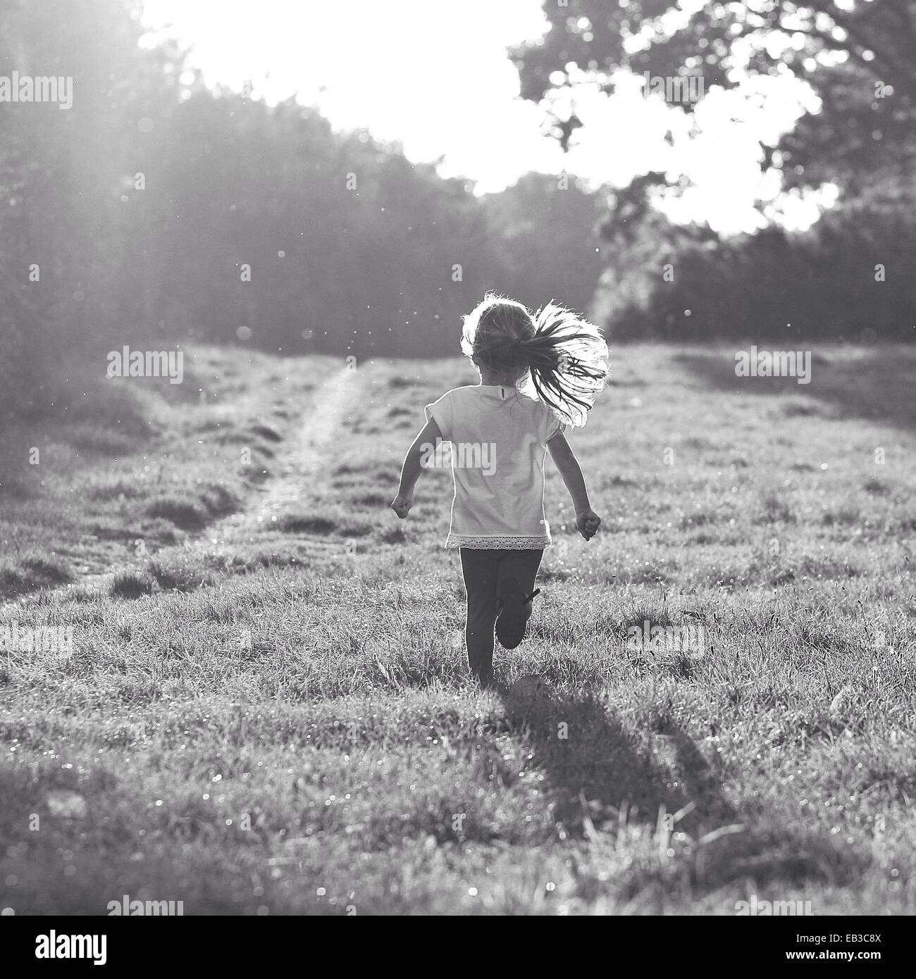 Rückansicht des Mädchen laufen in ländlichen Landschaft Stockbild