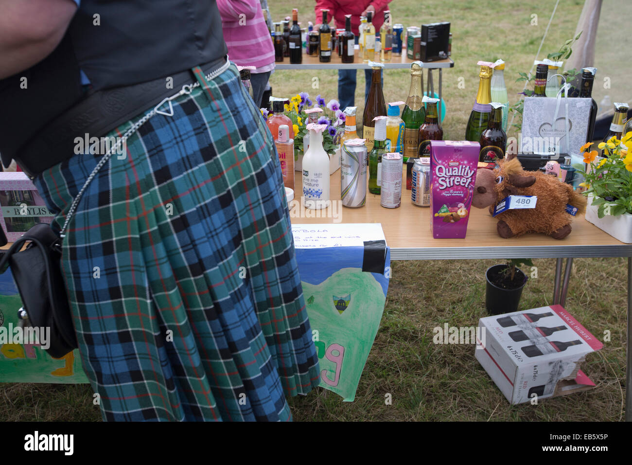 Ein Mann in einem schottischen Kilt, vorbei an einem Stall mit Tombolapreise auf dem Dalmally landwirtschaftliche Stockbild