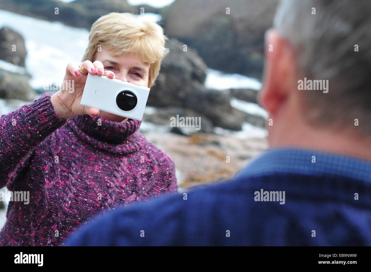 Frau, die Aufnahme des Mannes mit Smartphone Stockbild
