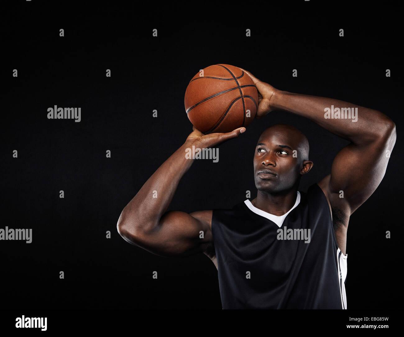 Young African American männliche Basketball-Spieler schießen auf den Reifen auf schwarzen Hintergrund Stockbild