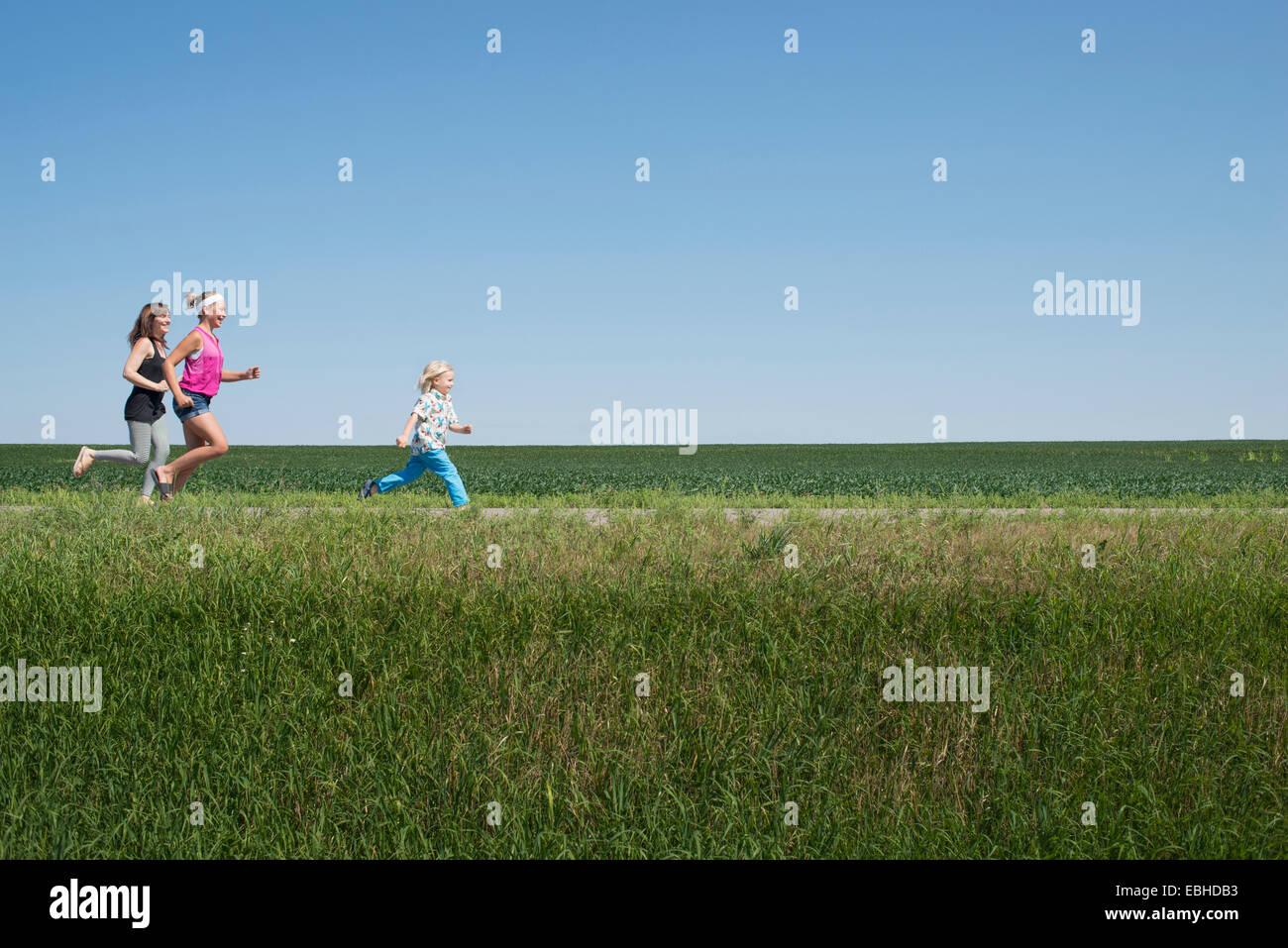 Drei Leute, die durch Feld Stockbild