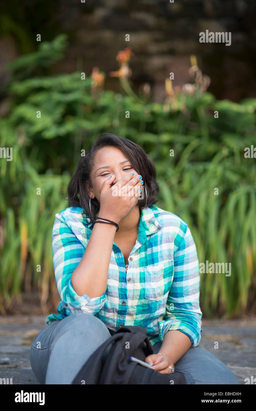 Junge Frau mit der Hand den Mund zu lachen Stockbild