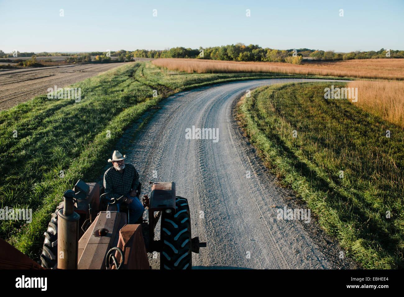 Erhöhte Ansicht der senior männlichen Bauer Traktor fahren auf der Landstraße, Plattsburg, Missouri, Stockbild