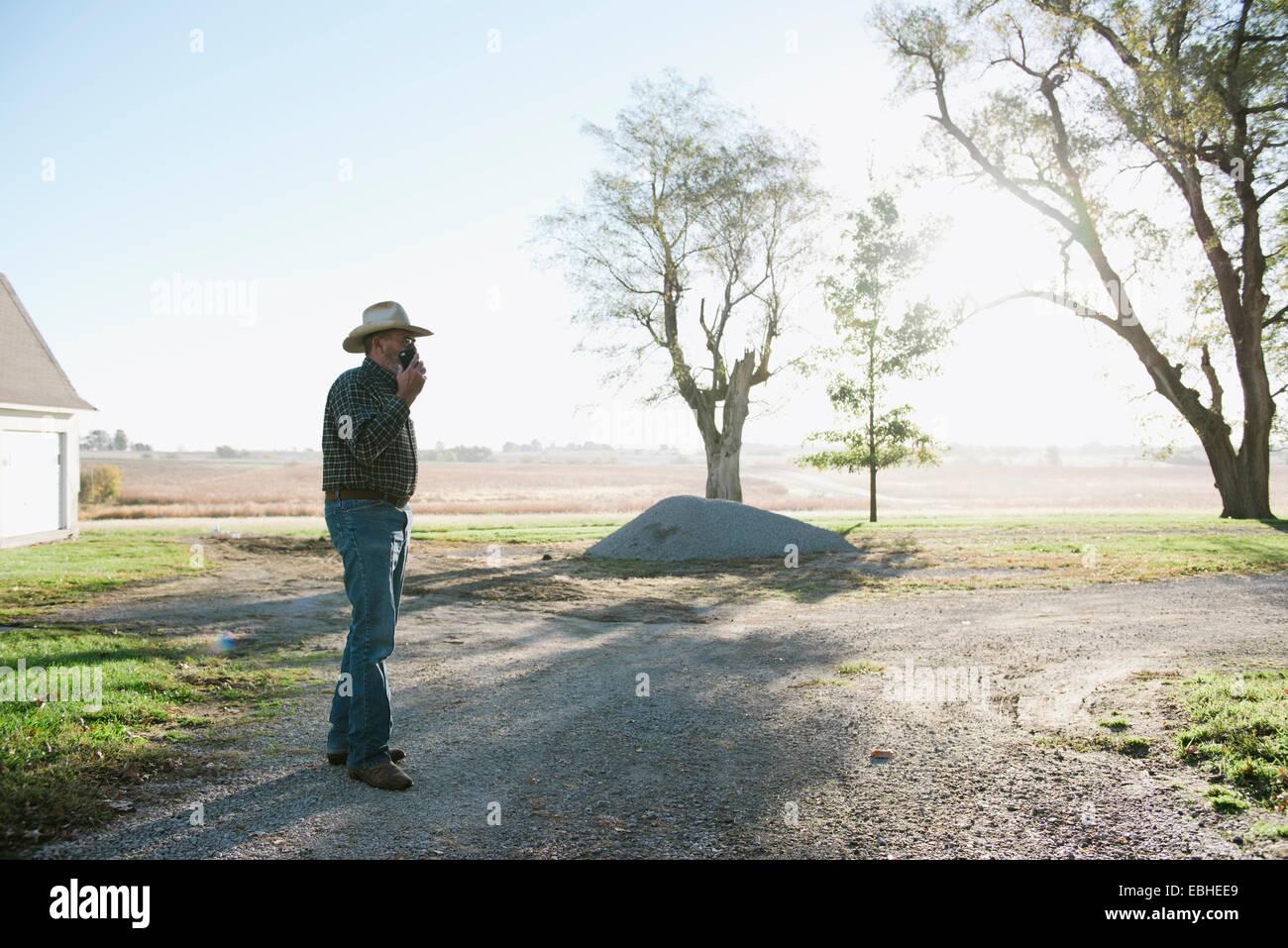 Senior männlichen Bauern im Chat auf Smartphone auf Feldweg, Plattsburg, Missouri, USA Stockbild