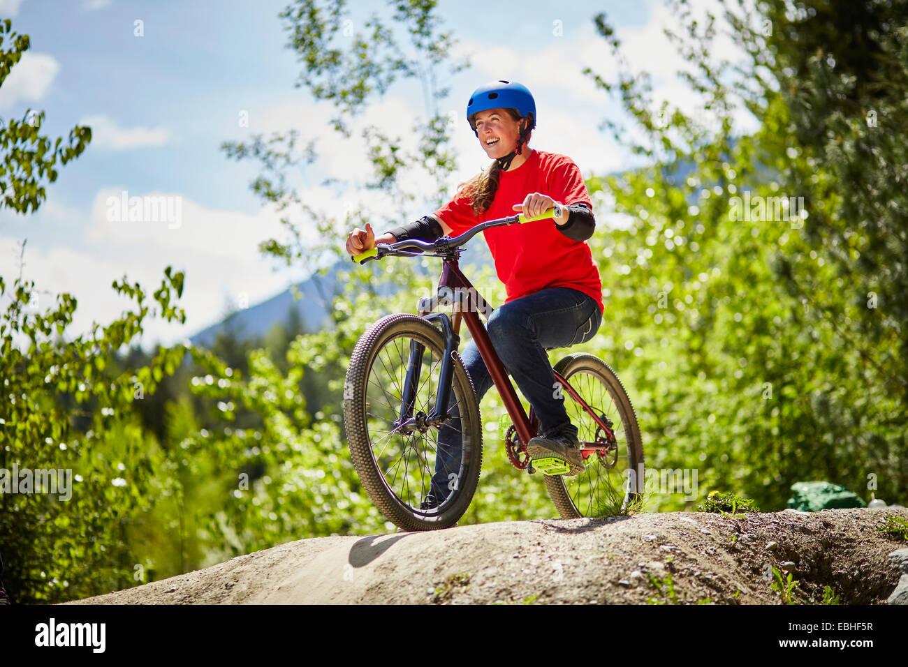 Junge weibliche bmx-Biker am Rand der Felsen im Wald Stockbild