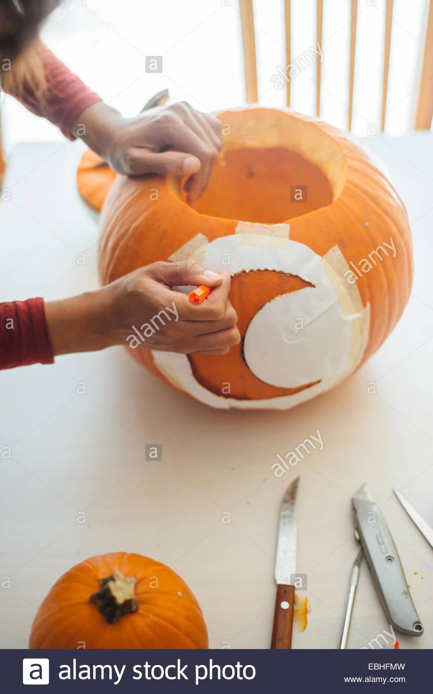 Junge Frau, die Zeichnung Gliederung der Mondsichel Schablone auf Kürbis in der Küche Stockbild