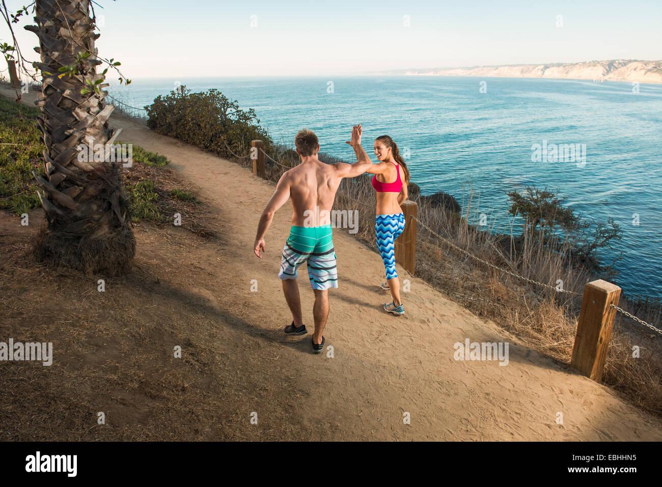Mitte erwachsenen Mann und junge Frau geben hohe fünf auf Weg vom Meer Stockbild
