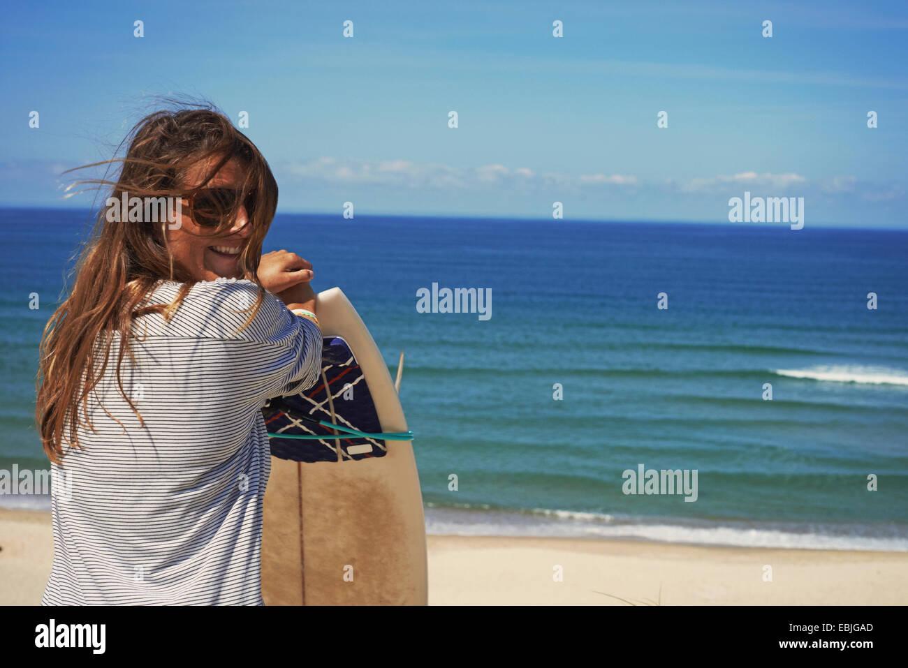 Frau mit Surfbrett am Strand, Lacanau, Frankreich Stockbild