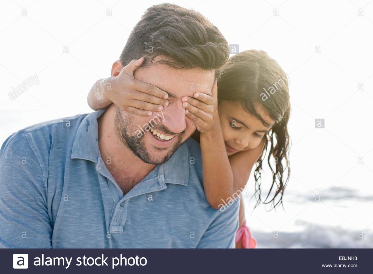 Mädchen mit Händen für Väter Augen am Strand, Toskana, Italien Stockbild