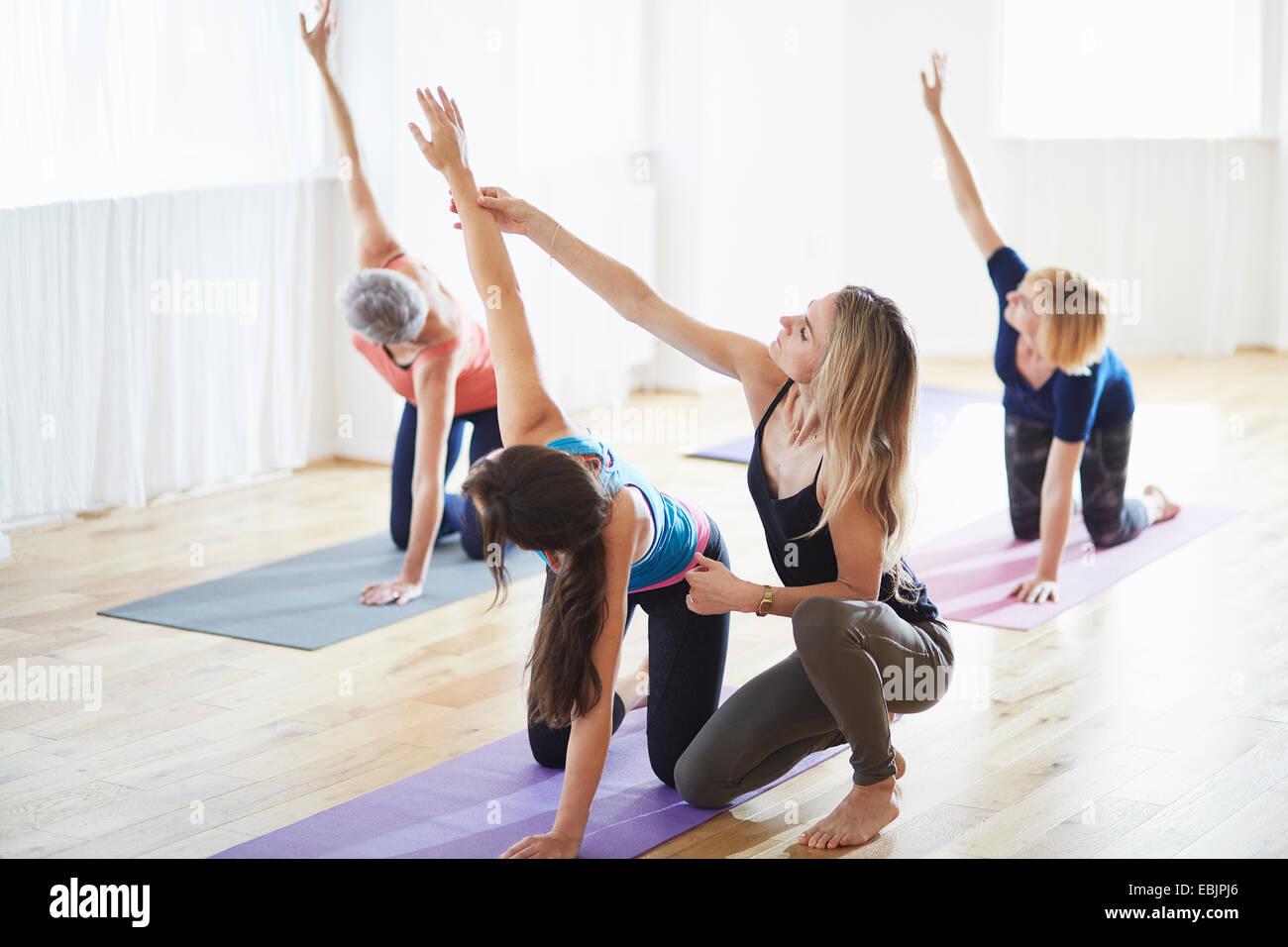 Frauen kniend und Arme in Pilates-Klasse Stockbild