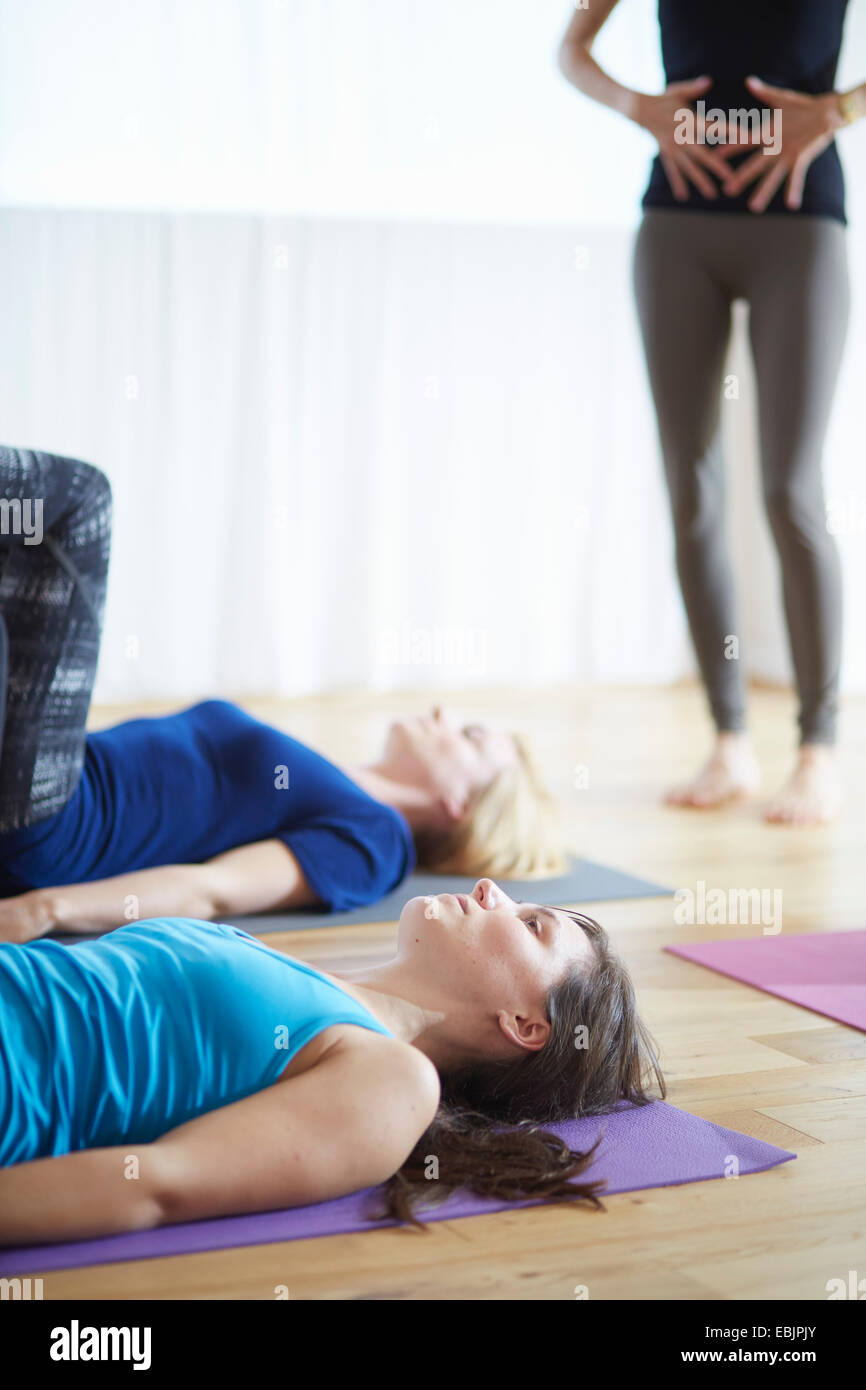 Lehrerin mit den Händen auf Bauch in Pilates-Klasse Stockbild