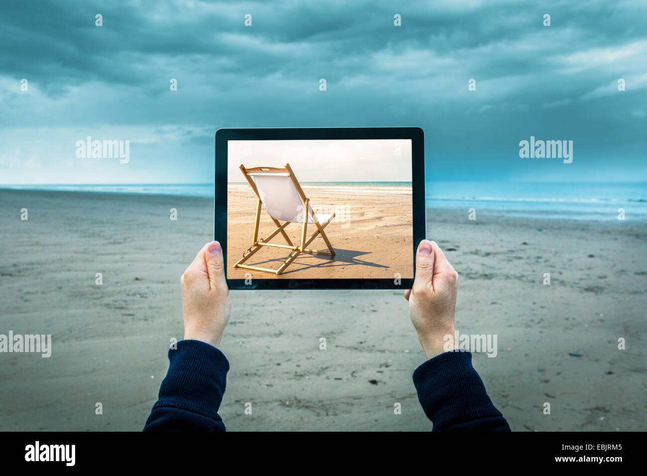 Reife Frau am bewölkten Strand hält digitale Tablet zeigt Sonnenstrand Szene, Fokus auf Hände und Stockbild