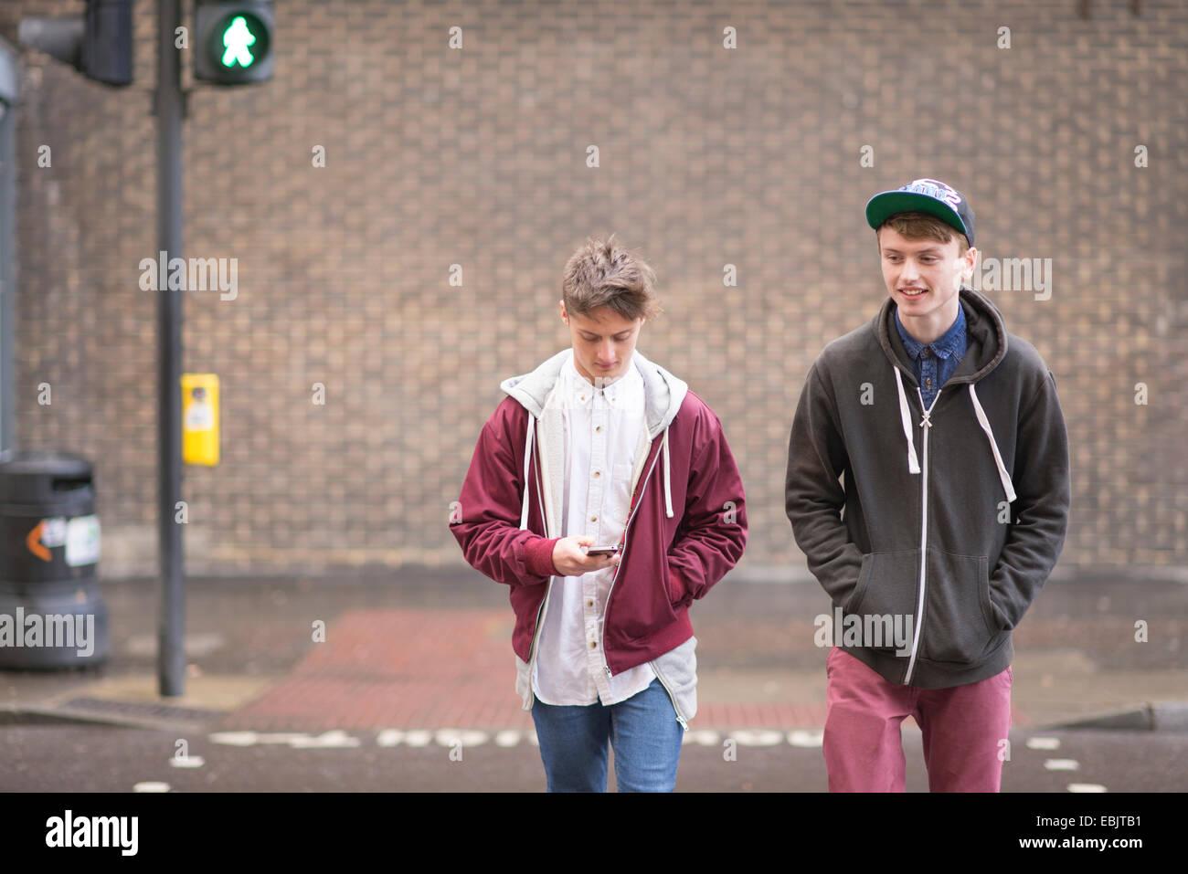 Zwei männliche Freunde, die Straße überqueren Stockfoto