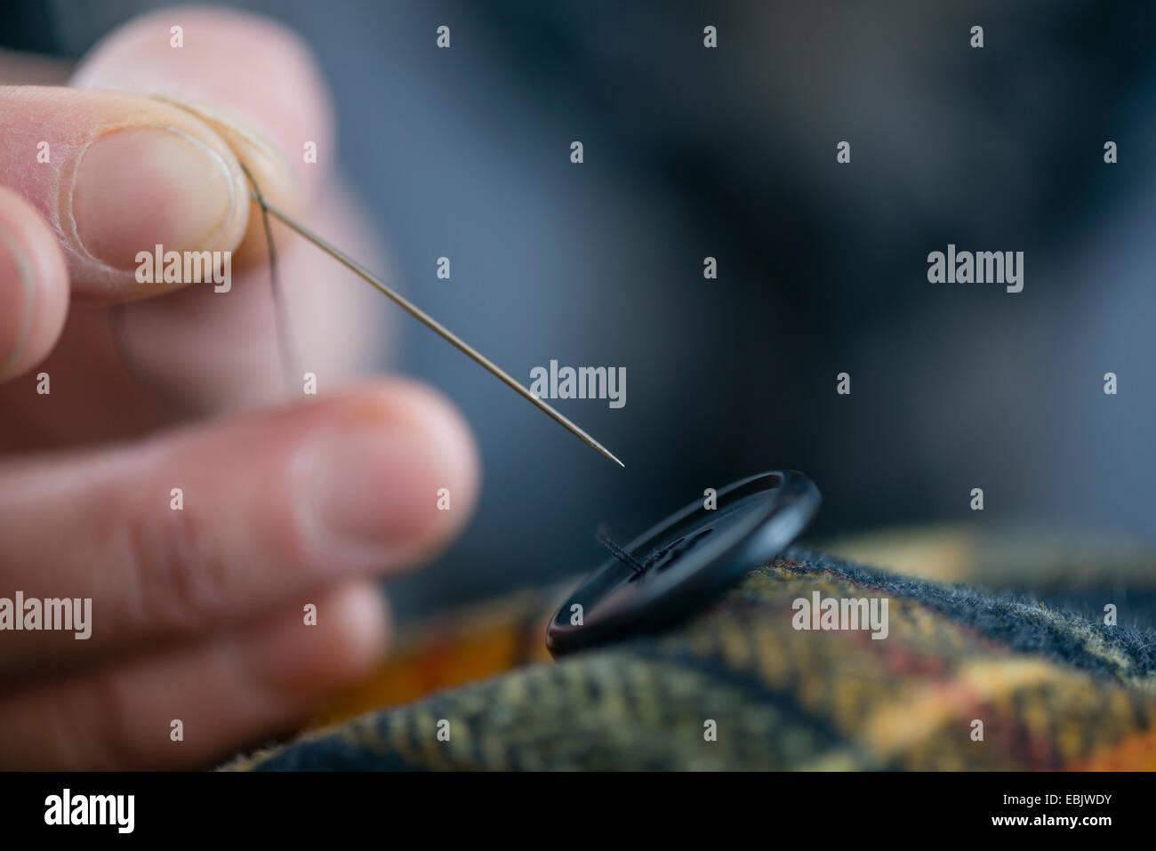 Schließen Sie Schneiderin Finger Nähen Taste auf Tartan in Werkstatt Stockbild