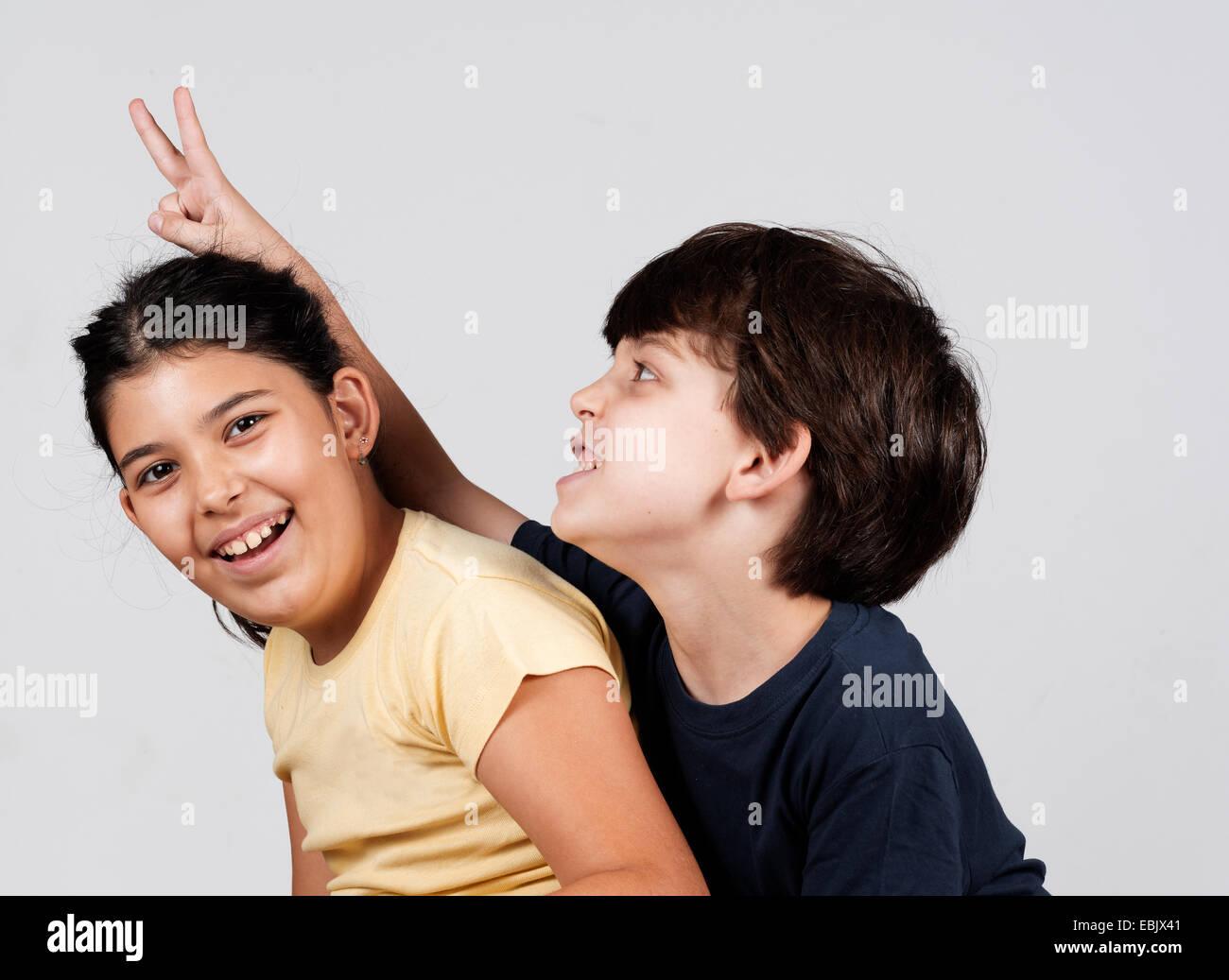 Jungen und Mädchen spielen, junge junge hält Finger als Hasenohren Stockbild