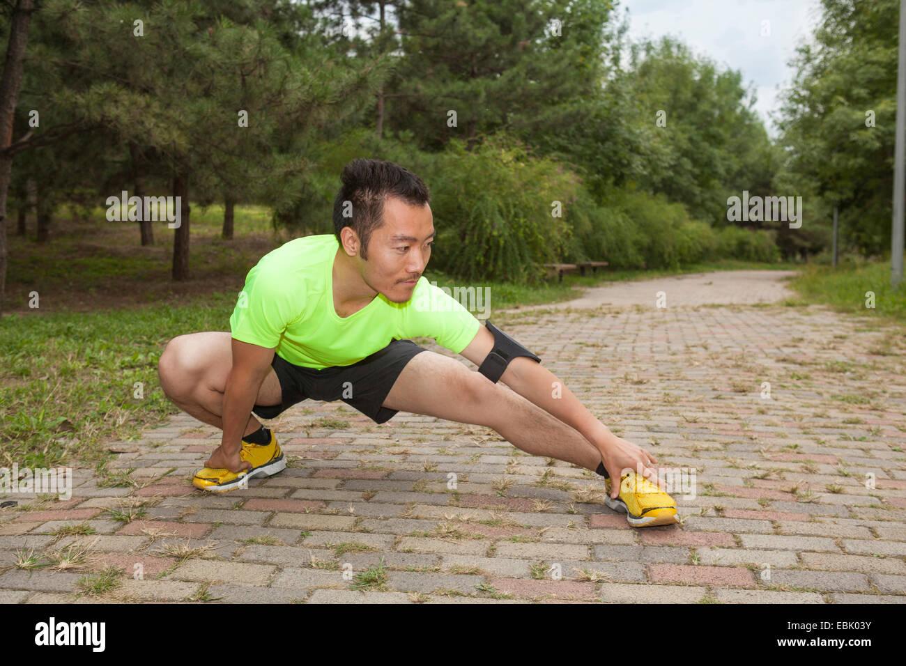 Junge männliche Läufer hocken und Strecken im park Stockbild