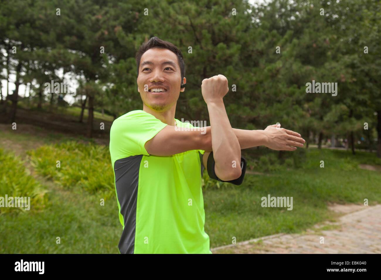 Junge männliche Läufer Strecken Arme im park Stockbild