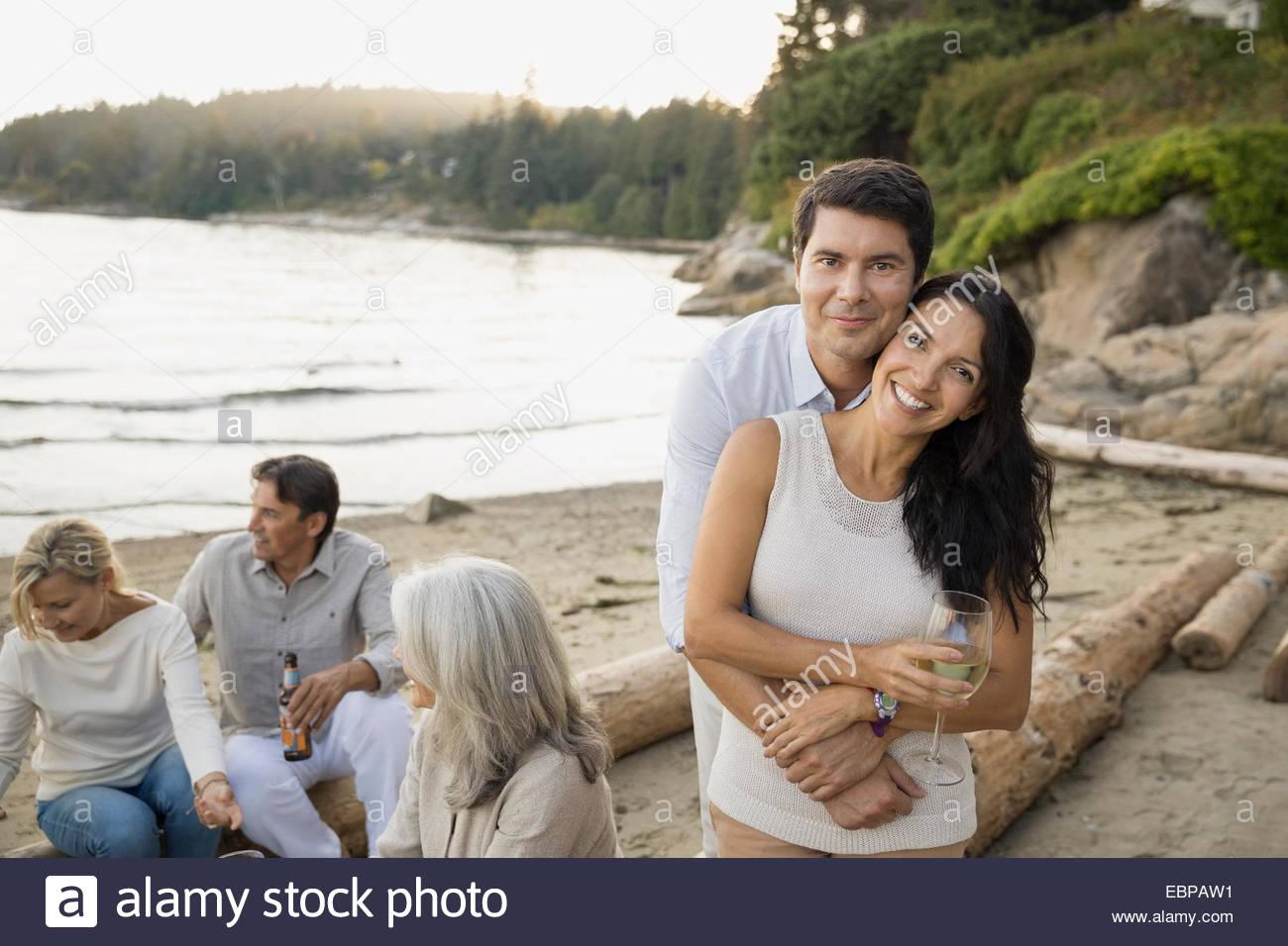 Porträt des Lächelns paar mit Freunden am Strand Stockbild