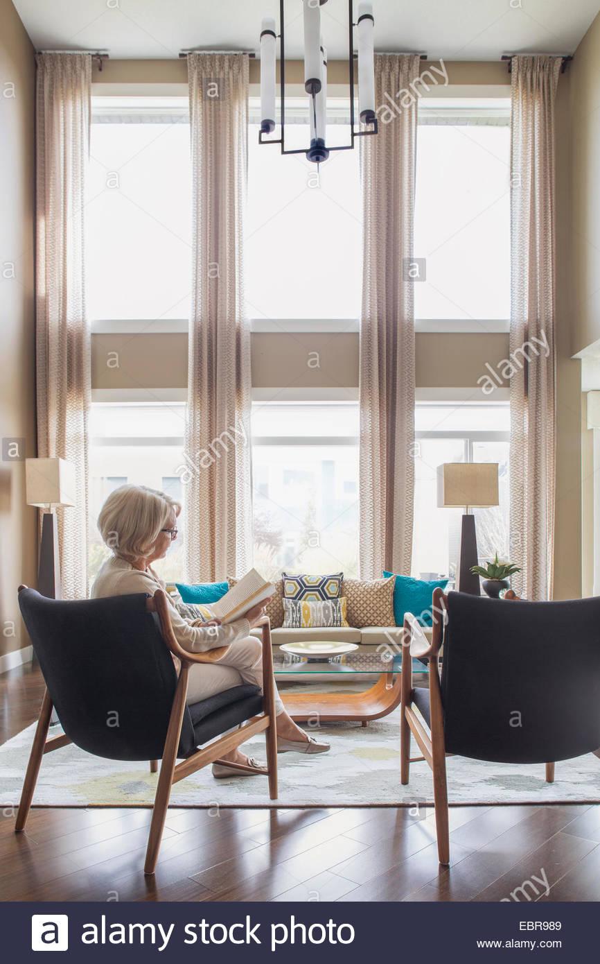 Frau Lesebuch in moderne Wohnzimmer Stockbild