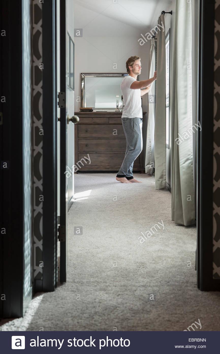 Mann schaut aus Schlafzimmerfenster Stockbild