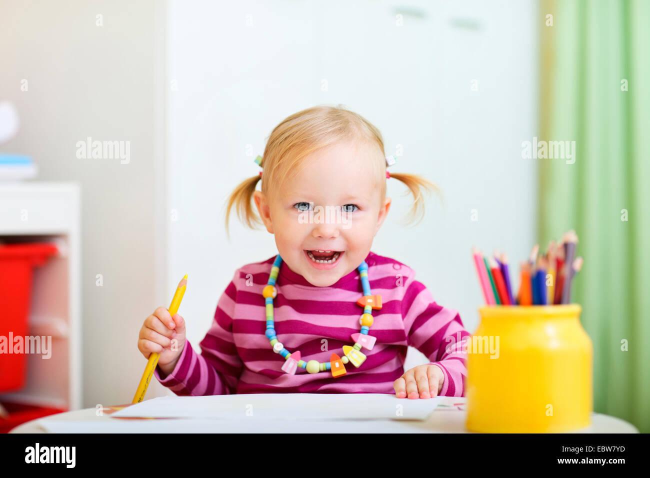 ein kleines Mädchen zeichnen mit Buntstiften Stockbild