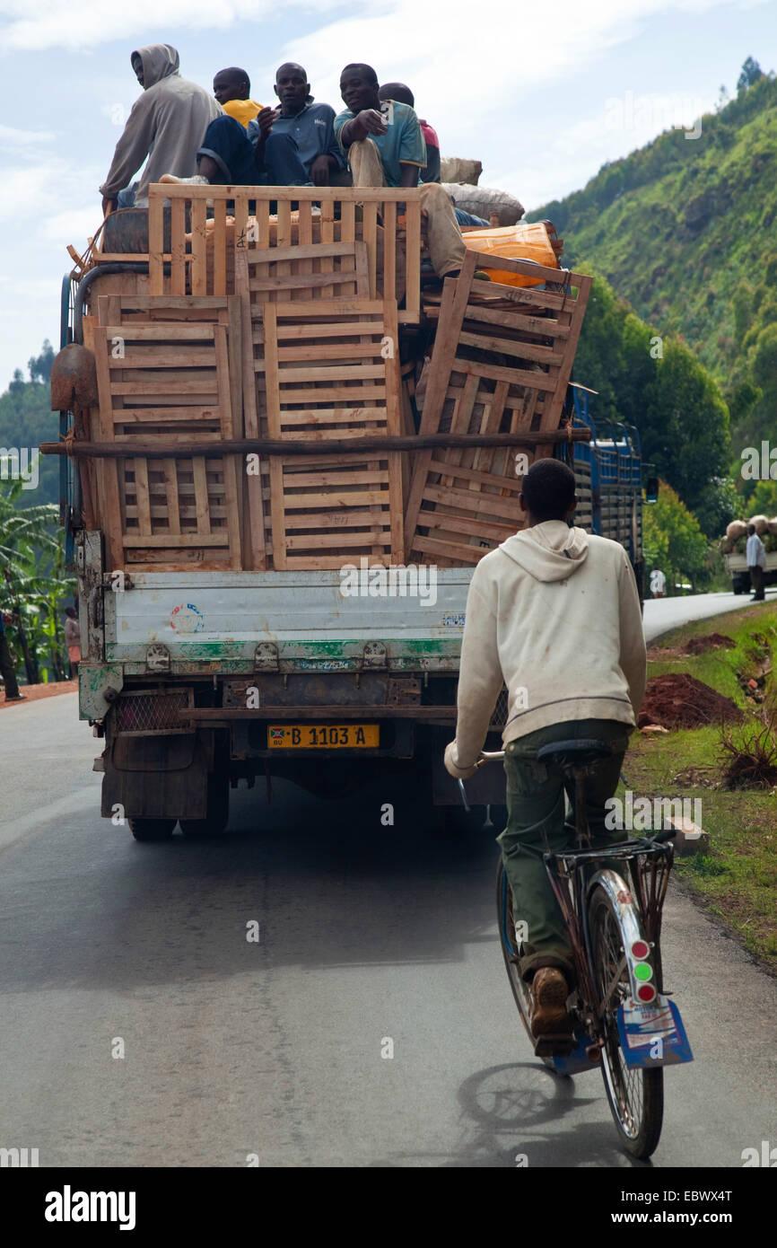 Biker hinter überladene Lkw auf kurvenreichen Straße, Burundi, Karuzi, Buhiga Stockbild