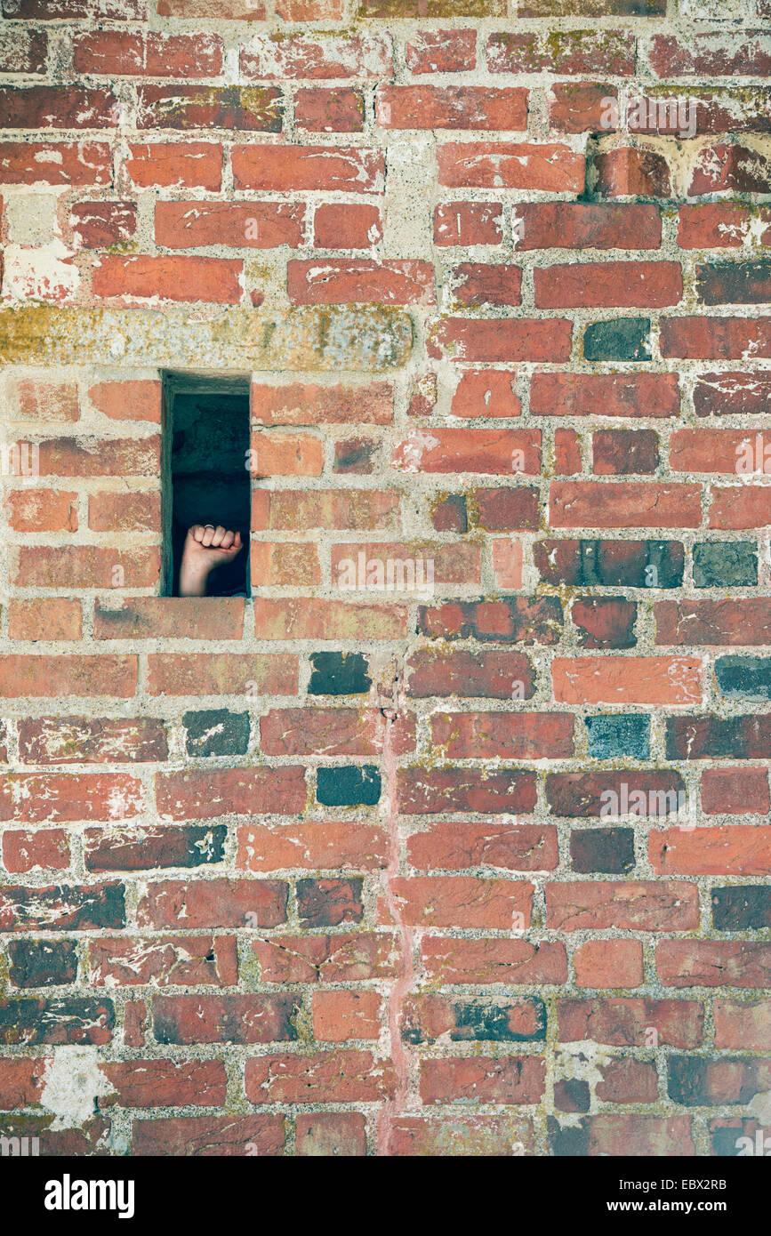 Hand eine Faust in die kleine Öffnung der Mauer machen. Konzeptbild von Protest, Gefängnis und politischer Stockbild