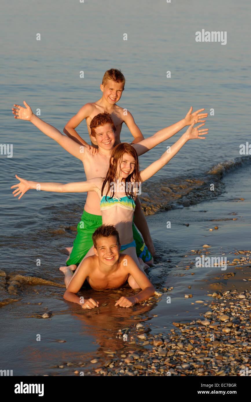 Italien, vier Kinder in einer Reihe am Meer Stockbild
