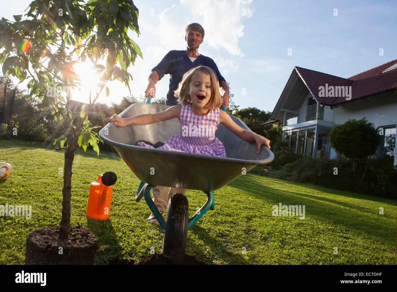 Vater mit Tochter in Schubkarre Baum im Garten Pflanzen Stockbild