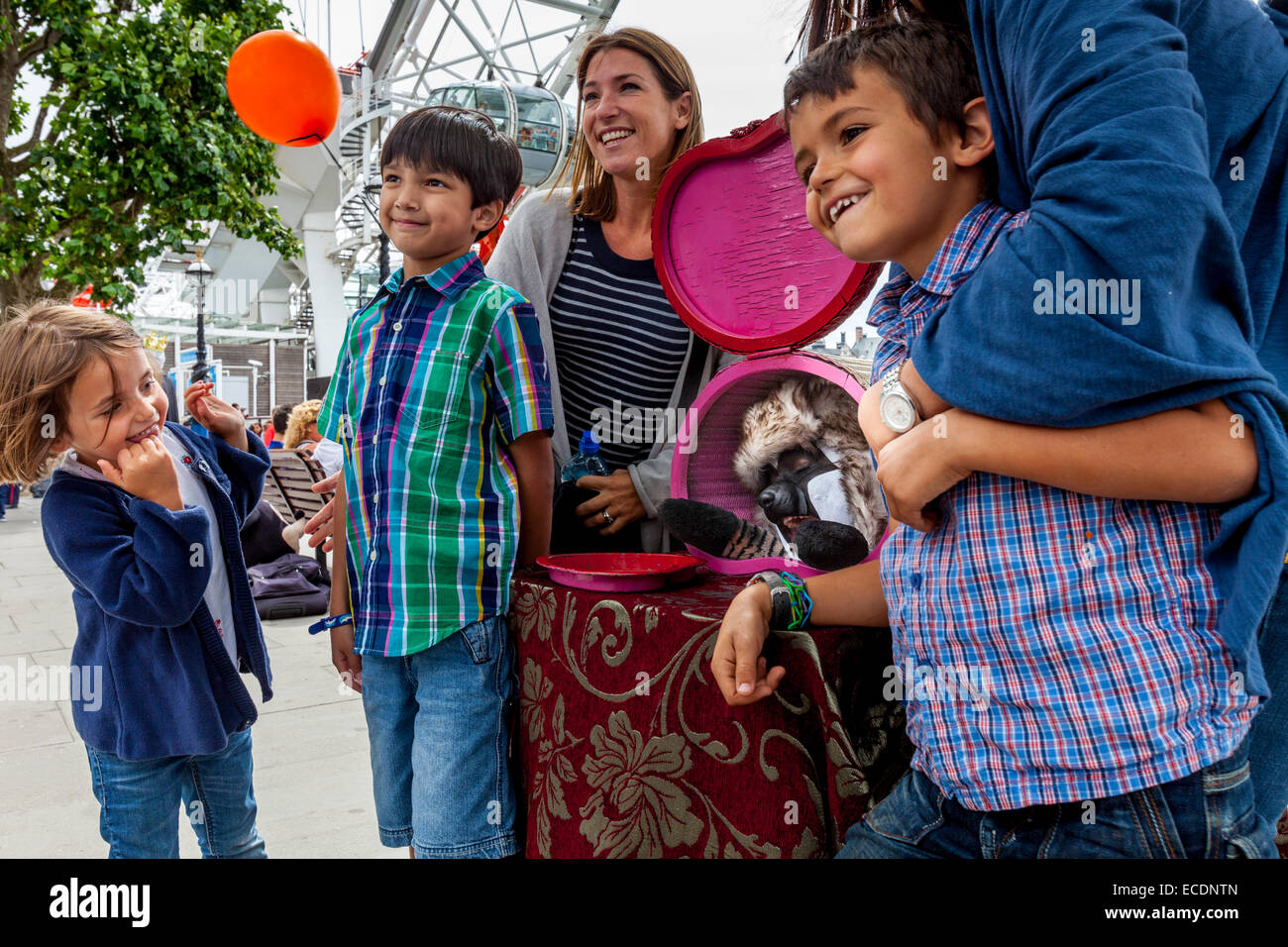 Eine Familie posiert mit A Street Entertainer auf der South Bank, London, England Stockbild