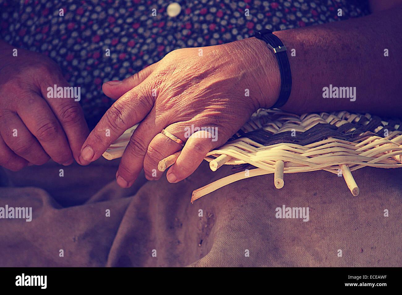 Nahaufnahme von weiblichen Händen weben Korb Stockbild