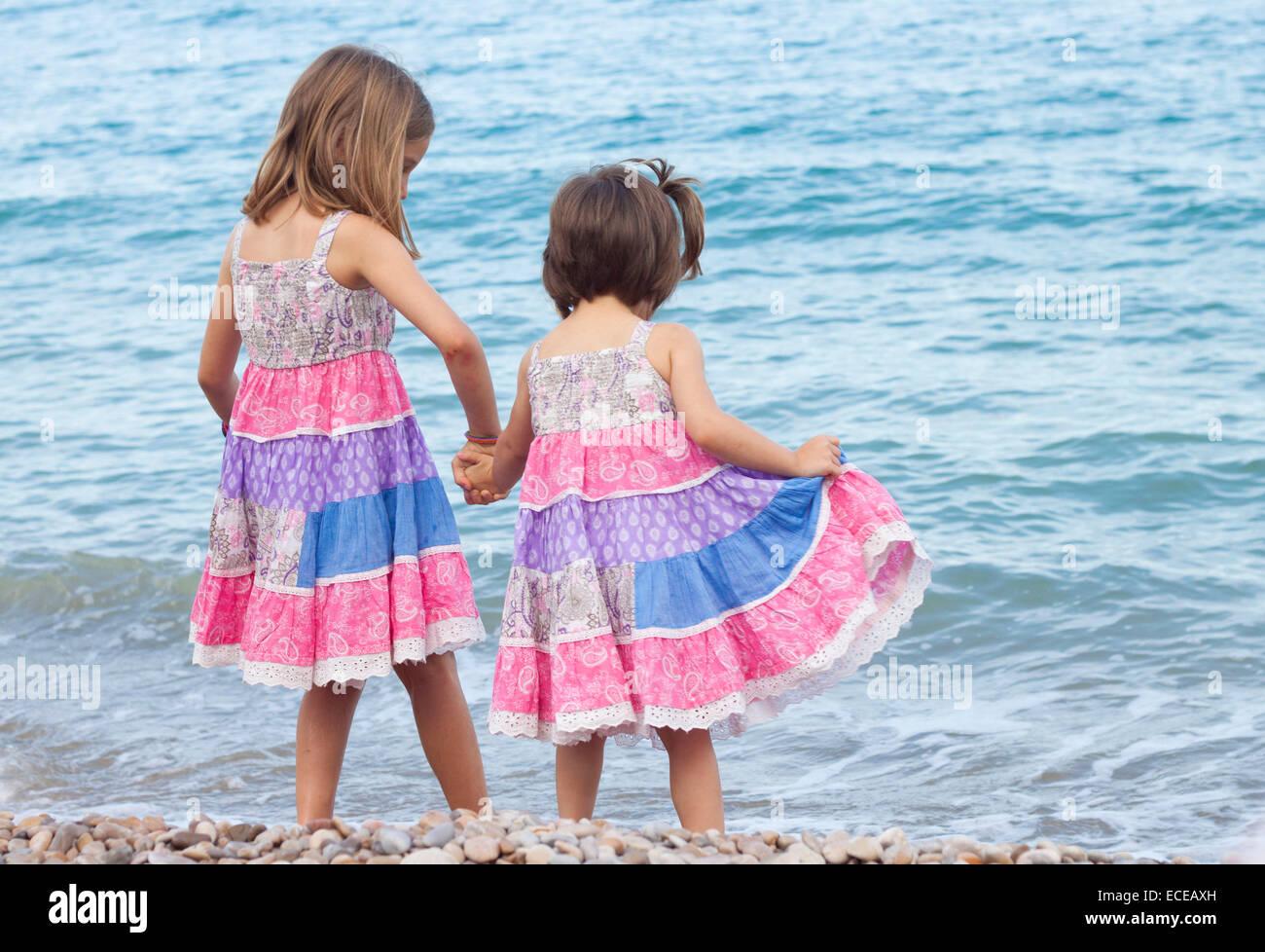 Zwei Schwestern stehen am Strand Hand in Hand Stockbild
