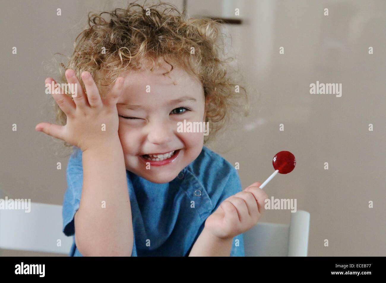 Mädchen (2-3) mit Lollypop lächelnd Stockbild