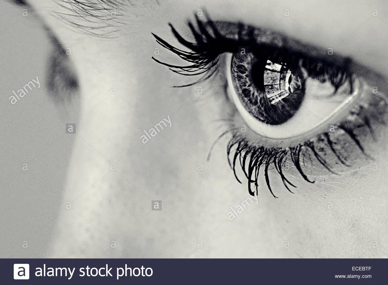 Nahaufnahme des Auges eines Mädchens mit einem Fenster spiegeln sich darin Stockbild