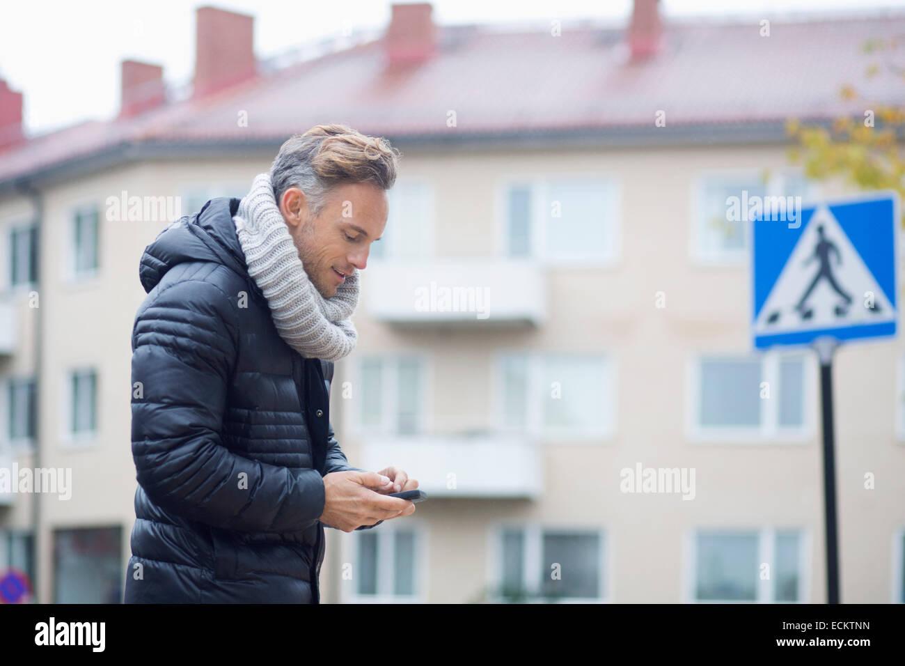 Reifer Mann mit Smartphone gegen Gebäude Stockbild